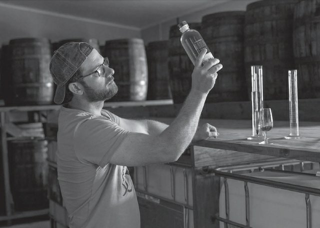 Trevor Bruns inspecting a bottle of rum