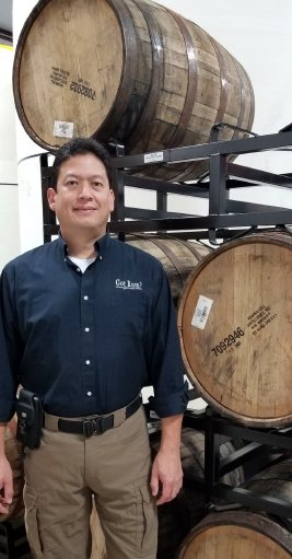 Luis standing by Rye filled barrels at Rum Central.jpg